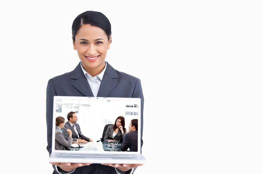 Thoughtful businesswoman talking to her team during a meeting against close up of smiling saleswoman presenting laptop screen