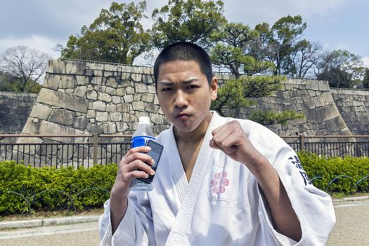 OSAKA, JAPAN - MARCH 25, 2012: Japanese teenager in karate fighter position. He is standing on the street, wearing kimono and pose straight to the camera