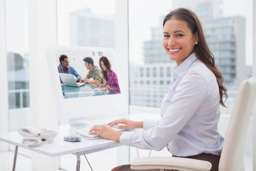 Creative team working together against smiling businesswoman working at her desk