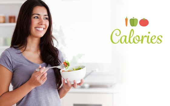 Calories against attractive woman enjoying a bowl of salad while standing