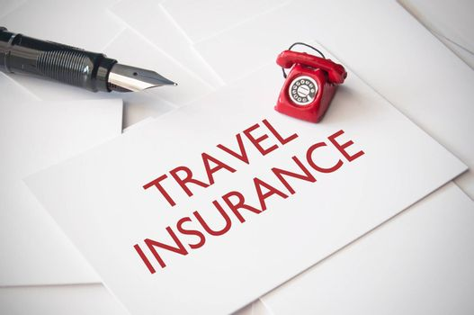 Small telephone on top of travel insurance business cards
