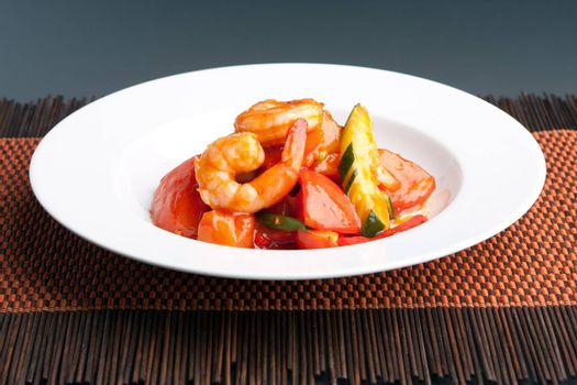 Thai style sweet and sour shrimp dish presented beautifully on a round white plate.