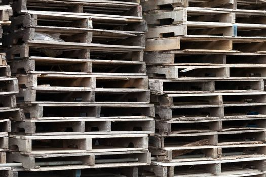 Piles of wooden pallets ready for breaking up and recycling into firewood kindling or DIY projects.