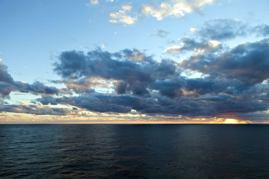 Sunset through the clouds over the Atlantic Ocean.