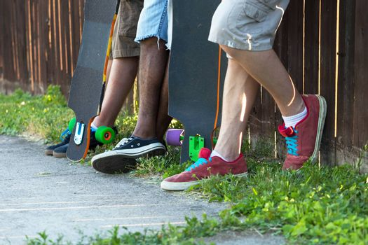 Longboarders feet standing along an urban fence line with their skateboards. Shallow depth of field.