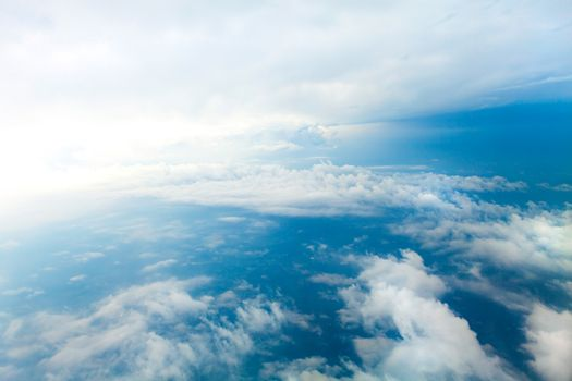 Aerial view of the blue skies and horizon with fluffy clouds and the earth below shot over Tennessee USA.