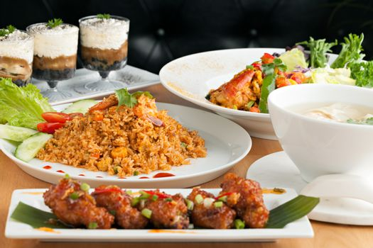Varieties of Thai foods and appetizers covering a table. Shallow depth of field.