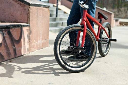 BMX bike rider parked at the skate park. Shallow depth of field.