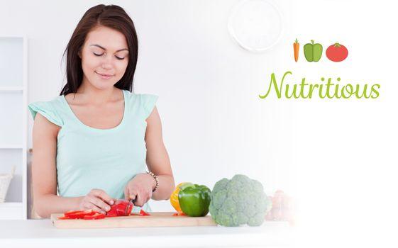 Nutritious against cute woman slicing a pepper