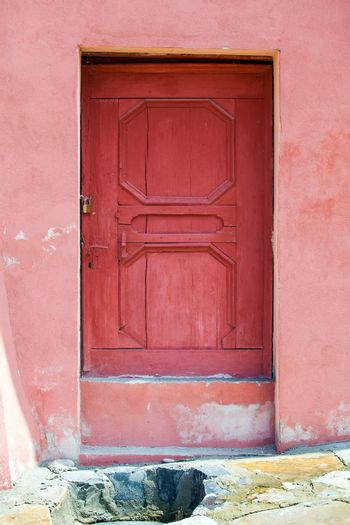 Turda, Romania - June 23, 2013: House facade with pink wood door fron Turda city, Romania
