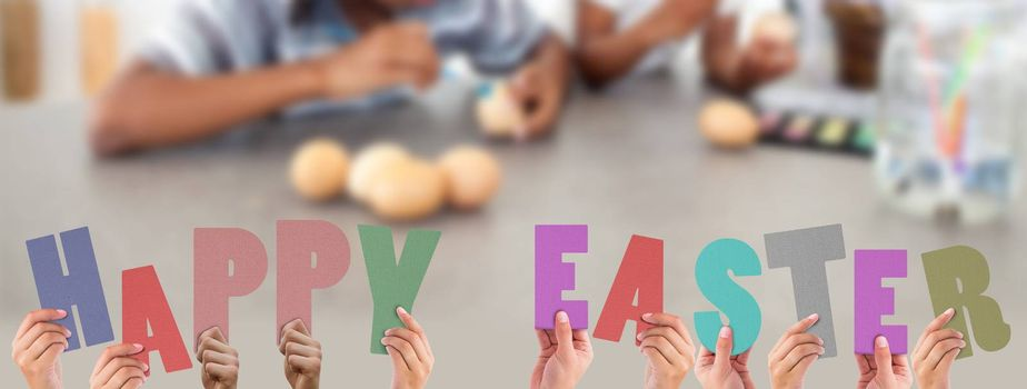 Hands holding up happy easter against concentrated siblings painting eggs