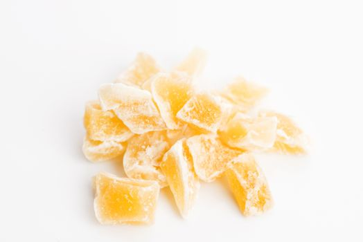 Caramelized ginger candy pieces isolated on white background