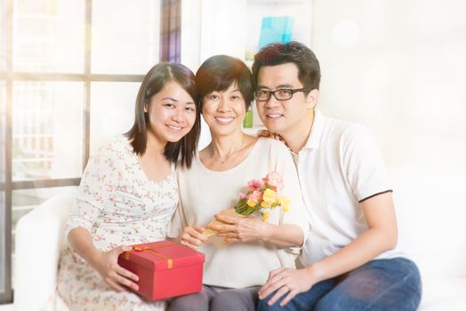 Happy mothers day. Asian senior mom received gift box and flowers from her young children. Family living lifestyle at home.