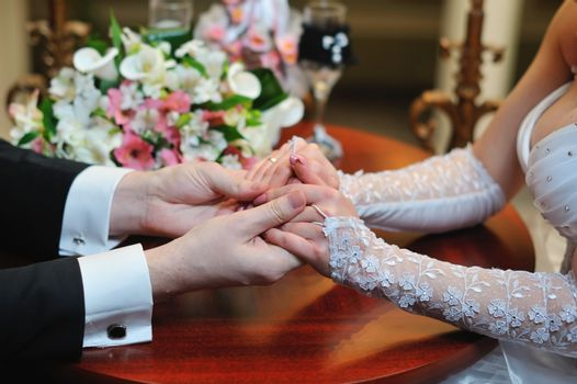 groom holds his bride's hand in appartaments.