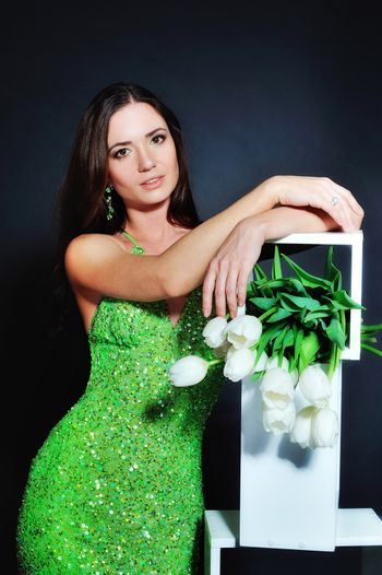 young lady with a bouquet of tulips on dark background.