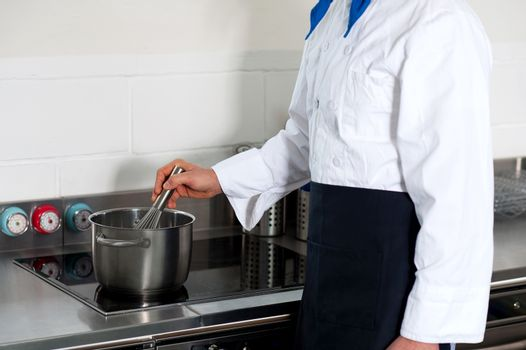 A cook prepares a dish in the kitchen