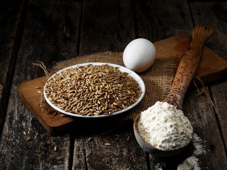 rye grain, egg, flour on the old wooden table