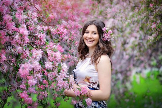 Beautiful woman walking in blossoming spring garden