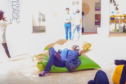 MILAN, ITALY - APRIL 16: Young man talking on smartphone while lying on green pouf at Tortona space location during Milan Design week on April 16, 2015