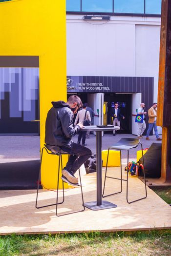 MILAN, ITALY - APRIL 16: Young man looking his smartphone while sitting at outdoor restaurant coffee open air cafe at Tortona space location during the Milan Design week on April 16, 2015