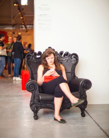 MILAN, ITALY - APRIL 16: Pretty young businesswoman reading message on smartphone while sitting at sofa during the Fuorisalone, Milan Design week at Tortona space location on April 16, 2015