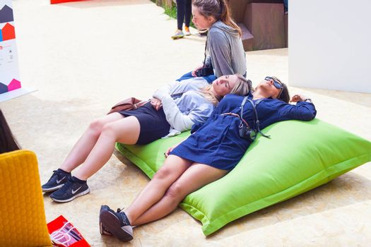 MILAN, ITALY - APRIL 16: Two young girls lie down on green pouf at Tortona space location during Milan Design week on April 16, 2015