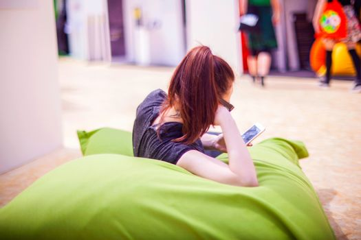 MILAN, ITALY - APRIL 16: Pretty woman reading message on smartphone while sitting on green pouf during Milan Design week on April 16, 2015