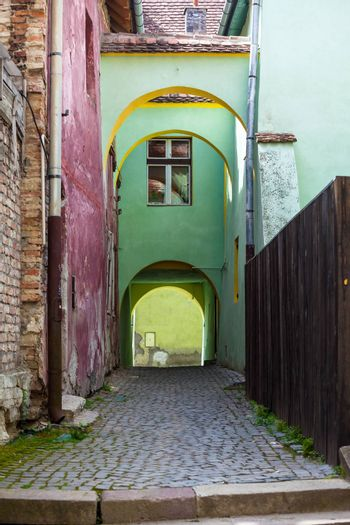 Sighisoara, Romania - June 23, 2013: Old stone paved street with arches from Sighisoara fortress, Transylvania, Romania