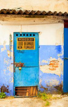 View of blue iron door with dangerous sign