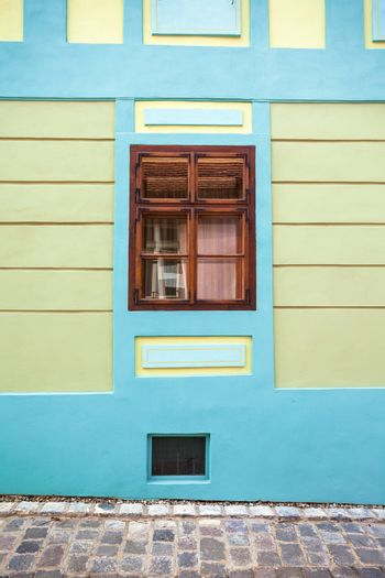 Sighisoara, Romania - June 23, 2013: Blue house facade with wooden window from Sighisoara city old center, Transylvania, Romania