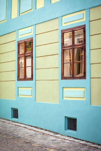 Sighisoara, Romania - June 23, 2013: Blue house facade with wooden windows from Sighisoara city old center, Transylvania, Romania