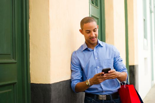 African American Man Shopping And Text Messaging On Phone