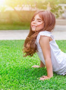 Little girl doing push-ups outdoors