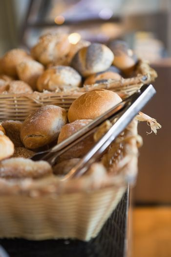Basket with fresh bread and tongs