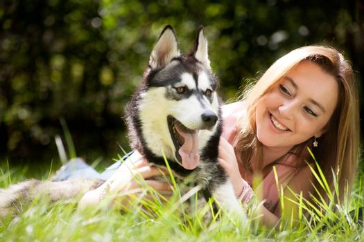Young woman and her husky in the forest