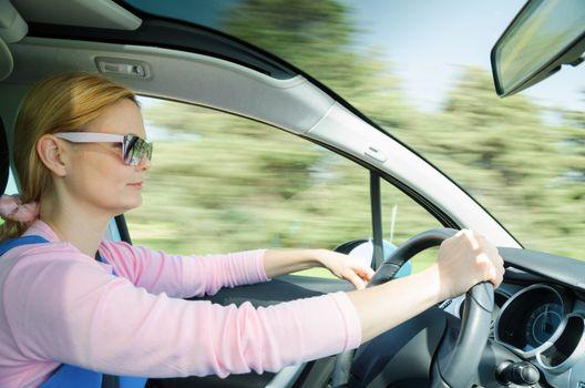 Pretty woman in sunglasses driving fast car