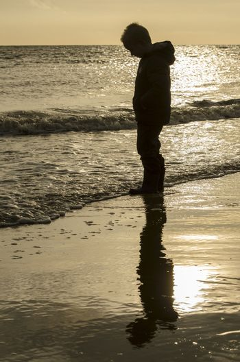 Silhouette and reflection of a little boy on the beach.