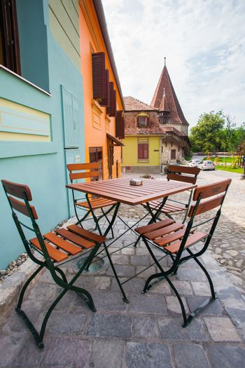 Sighisoara, Romania - June 23, 2013: Table with chairs on stone paved old street and colored houses from Sighisoara fortresss, Romania