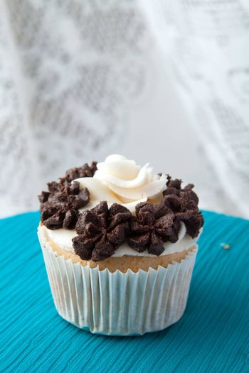 Close up of a decadent gourmet cupcake with chocolate and vanilla frosting.
