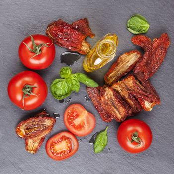Sundried and fresh tomatoes with fresh basil leaves on stone background, top view. Culinary italian eating.