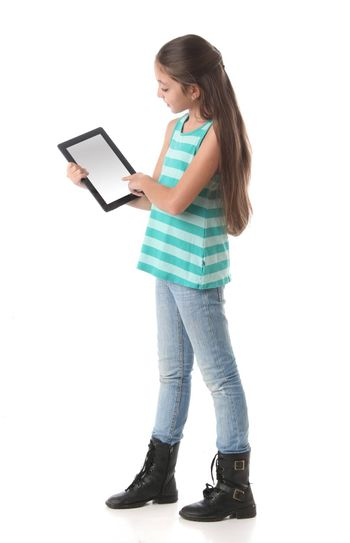 Beautiful pre-teen girl using a tablet computer. Clipping path for the screen