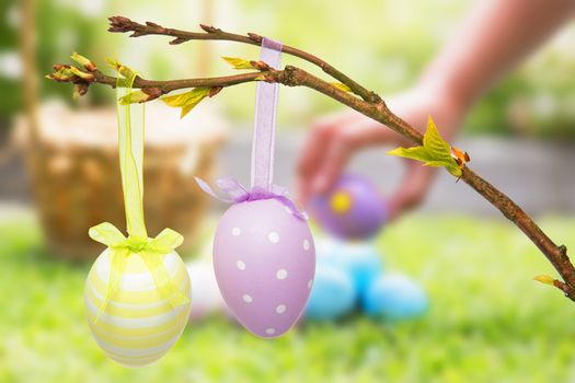 Little girl collecting easter eggs  against hanging easter eggs