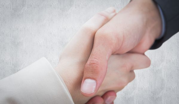 Close up on new partners shaking hands against white background