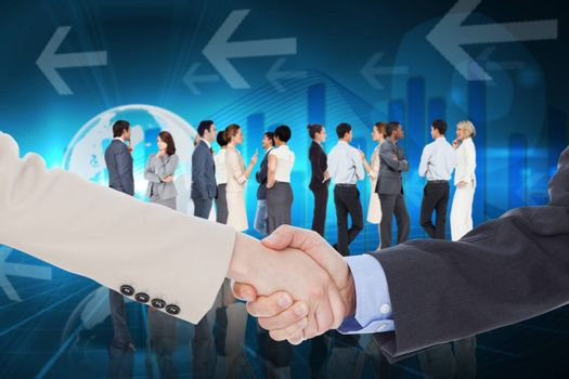 Smiling business people shaking hands while looking at the camera against global business graphic in blue