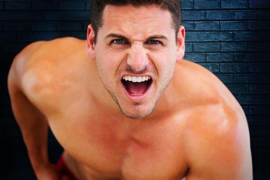 Bodybuilder shouting against black background