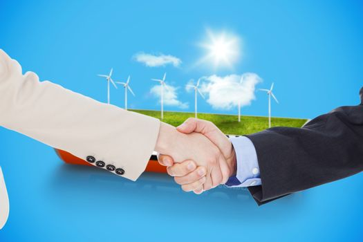 Smiling business people shaking hands while looking at the camera against wind turbine field in an energy saving battery