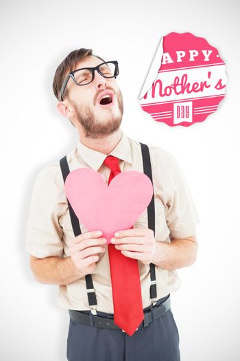 Geeky hipster crying and holding heart card against mothers day greeting