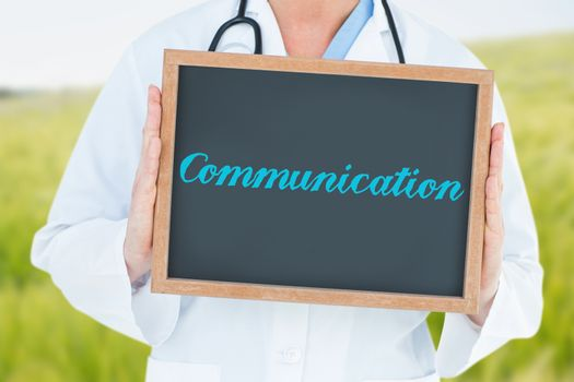 The word communication and doctor showing chalkboard against green meadow