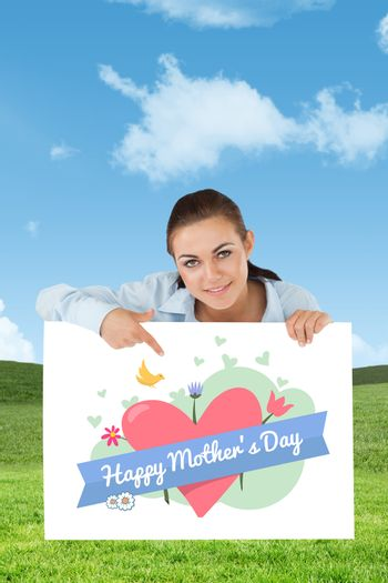 Businesswoman pointing on sign under her against field and sky