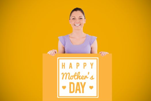 Portrait of a charming woman posing behind a billboard while standing against yellow background with vignette